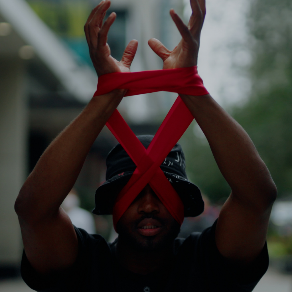 Man with his hands wrapped in red ribbon.